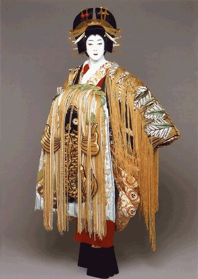 Kimono of an Oiran, the very top of the ladder in the Floating World. Different from Geisha, these women's role was sexual pleasure, and their obi were always tied in front. Additionally their hair and furnishing are much more elaborate.