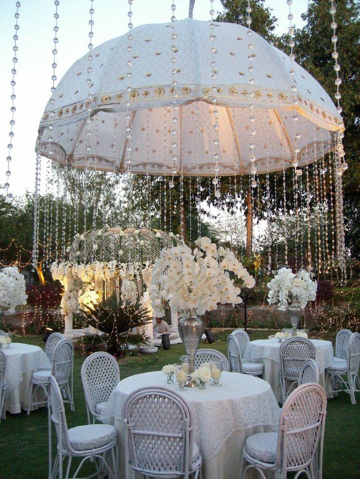 Decoração super diferente de um casamento no campo. Os fios de cristais lembram a chuva caindo sob o guarda-chuva branco e trazem magia ao visual da festa.