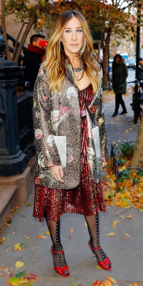Thanksgiving fashion inspo, brought to you by Sarah Jessica Parker, who delivered another one of her signature, wonderfully eccentric style for an appearance on The Tonight Show Starring Jimmy Fallon: a scarlet red velvet dress topped with a metallic floral jacquard coat, a stack of layered chains, and a chain-strap cross-body.