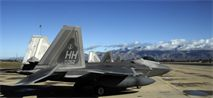 Three F-22 Raptors from Hickam Air Force Base, Hawaii, are parked on the flightline at Davis-Monthan Air Force Base, Ariz., March 2, 2014. Four F-22's were diverted to D-M and during landing, three of the Raptors' right side tires deflated as a safety precaution due to an increase in tire pressure, caused by the weather conditions and landing friction. (U.S. Air Force photo/Staff Sgt. Angela Ruiz