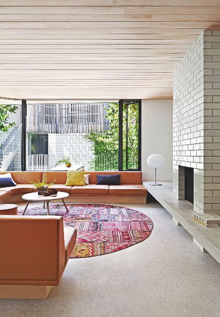 This Midcentury-inspired living room is a trove of good design ideas, from the tiled chimney to the wood-clad ceiling. We love the bright orange sofa. Image: Livingetc