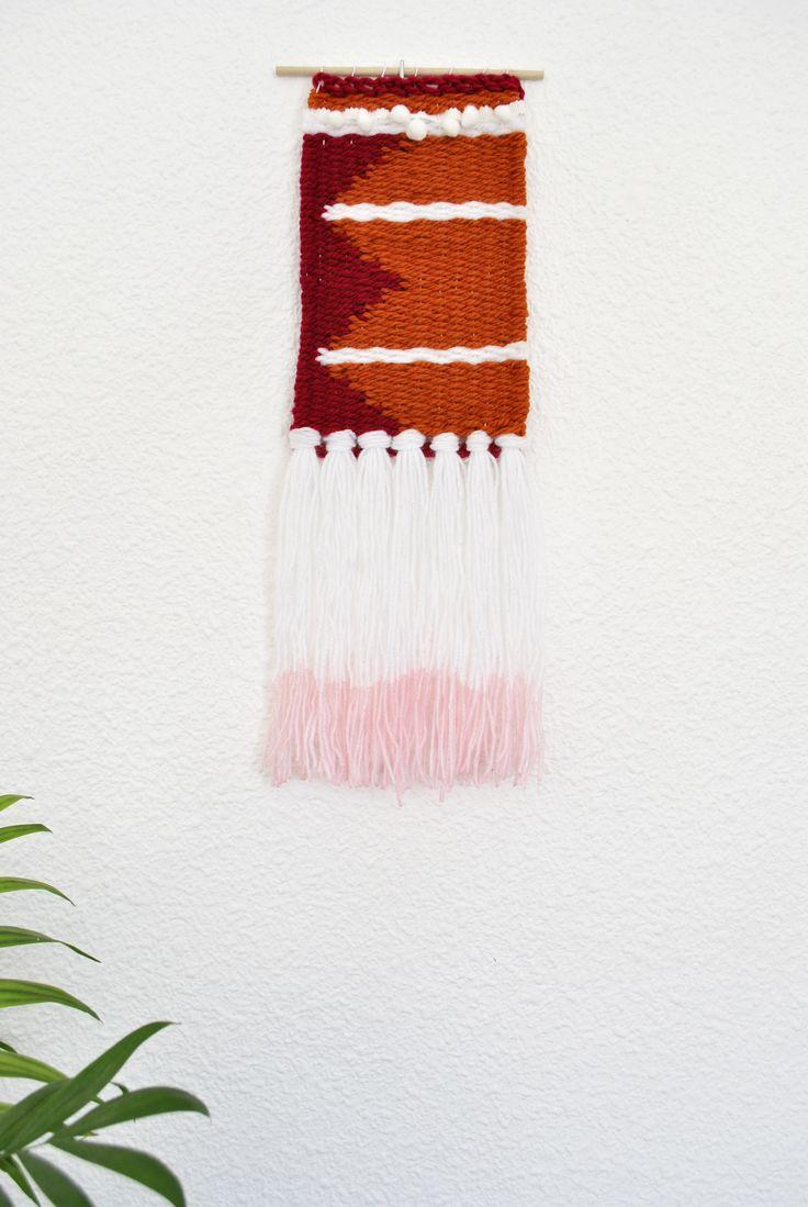 Hecho totalmente a mano con amor ❤ y en un ambiente sin humos.Ideal para colgar en la pared y formar parte de la decoración en casa. Tejido en una unión de colores y lanas, en granate, blanco y naranja, con los flecos teñidos en rosa por la parte de abajo y pompones color blanco como detalle superior.Sujeto en una varilla redonda de madera natural y con hilo egipcio para poder colgarlo de ahí si lo prefieres.Dimensiones - Largo: 40cm con flecos / 22cm sin los flecos...