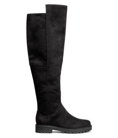 Schwarz. Warm gefütterte Stiefel aus Velourslederimitat. Kniehoher Schaft mit Elastikeinsatz und Reißverschluss an der einen Seite. Futter und Innensohle