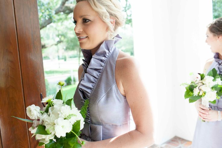 bridesmaid in lavender carries her bouquet of white cymbidium orchid, white akito roses, white dahlia, white ranunculus, , monkey tail fern, galax leaf, fox tail fern and lemon leaf.