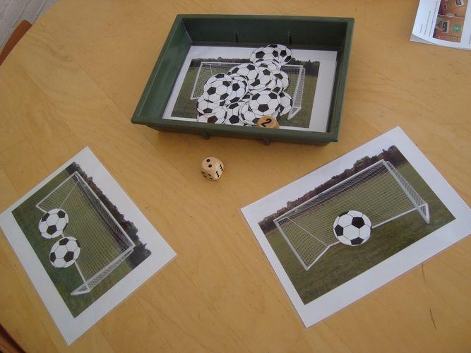 Rekenen jongste kleuters: voetbaldobbelspel. Evenveel voetballen in je doel leggen als stippen op de dobbelsteen. Wie heeft meer/minder voetballen in zijn doel?