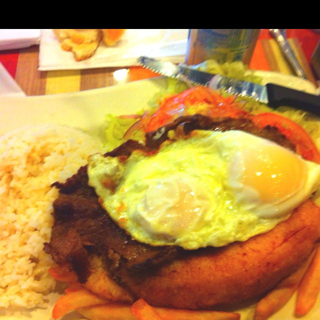 Bisteck a lo pobre - Peruvian. Fried pepper steak, fried banana, French fries, topped with a fried egg. Yummmy
