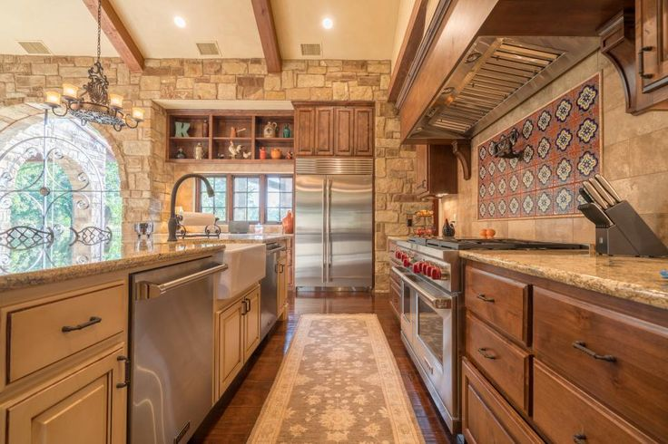 This galley kitchen features neutral stone walls paired with stainless steel appliances, including two dishwashers. Granite countertops are paired with brown wood and neutral painted cabinets, while colorful Mediterranean tiles cover the backsplash area.