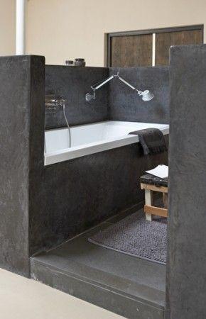 Afgeschermde badkuip met aan de andere kant de wastafel