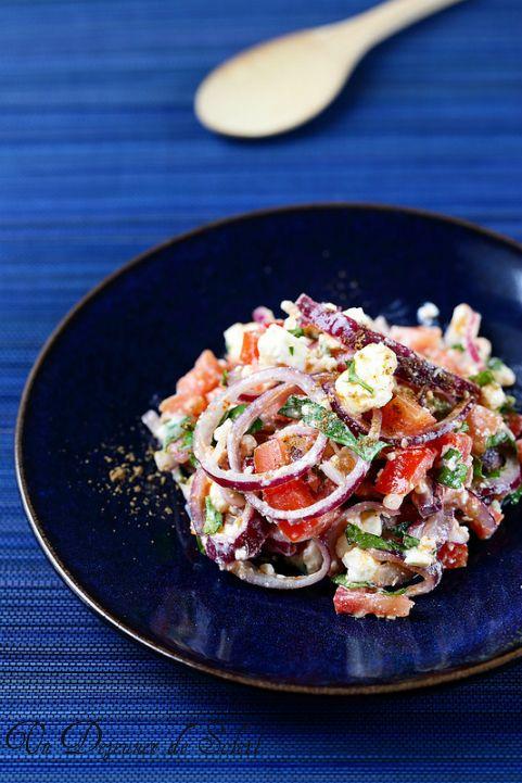Salade turque  Salade aux oignons rouges, féta, coriandre et épices (pour 4 personnes)      200 g de féta (si possible du fromager)     3 tomates en grappe (les plus mûres possible)     1 gousse d'ail nouveau (plus si on aime)     1 gros oignons rouge ou 2 petits (le plus doux possible)     1 càc de sumac, 1/2 càc de paprika, une pincée de coriandre     les feuilles 1/2 bouquet de persil et 1/2 bouquet de coriandre     huile d'olive vierge extra, sel et poivre