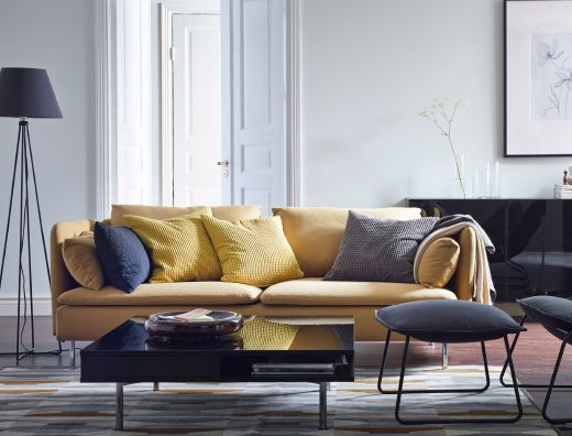 A modern living room with a yellow SÖDERHAMN sofa, VILSTAD armchair and footstool in black, and a black TOFTERYD coffee table