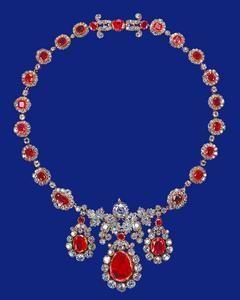 Este collar fue adquirido por la Reina en 1964. Anteriormente pertenecía a la colección Baring. Se cree que los tres colgantes centrales - cada uno de un rubí de corte plano rodeado de brillantes - se utilizaron originalmente como un par de pendientes y un colgante antes de que se convirtieron en colgantes en este collar de rubí y racimos de diamantes separados por diamantes individuales.