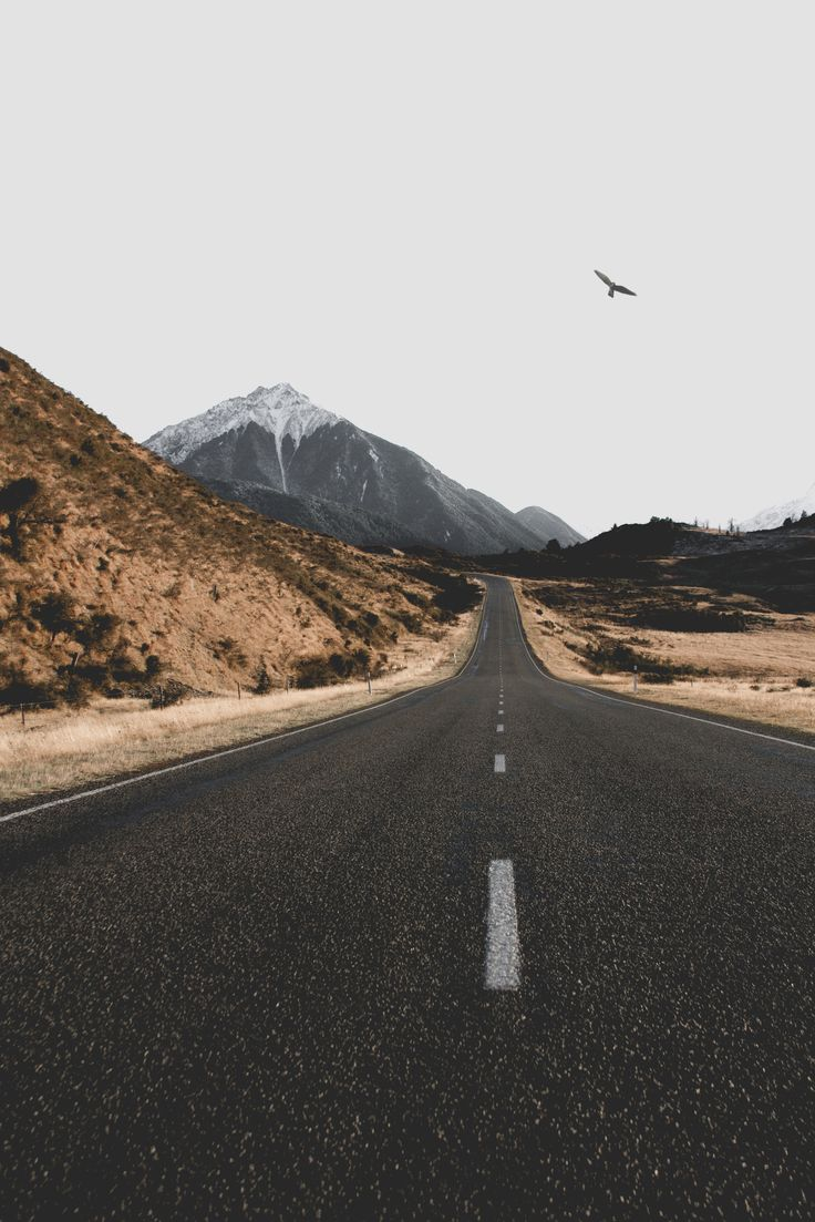 An empty asphalt road with a mountain on the horizon in Arthur's Pass