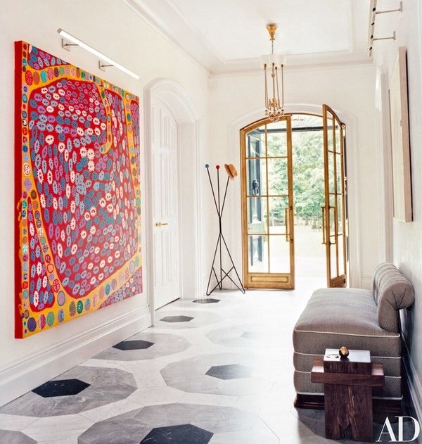 A painting by Yayoi Kusama commands a wall in the entrance hall/gallery, which is paved with Carrara, Bleu de Savoie, and Nero Marquina marbles in a graphic pattern   archdigest.com