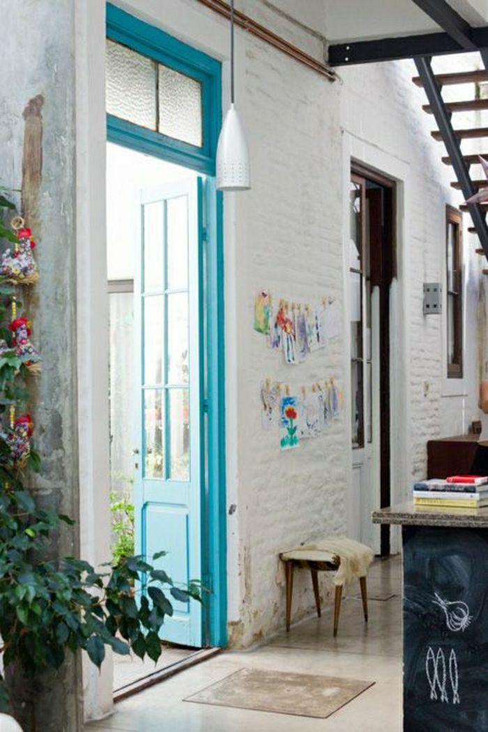 une belle porte d'entrée en bois de couleur bleu cyan, mur de briques blancs, escalier,