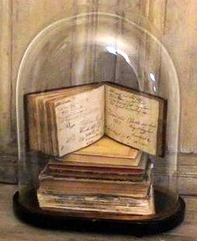 Beautiful display of old books under a glass dome.