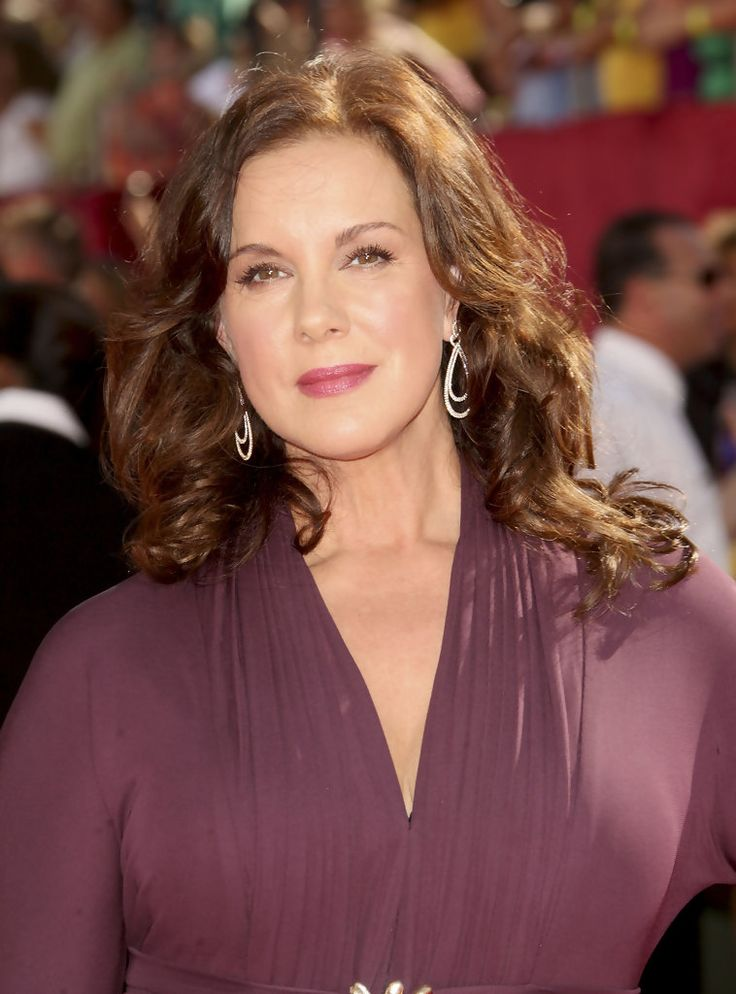 Elizabeth Perkins is radiant and elegant with shoulder-length curls that are pulled back slightly to reveal her dramatic ...