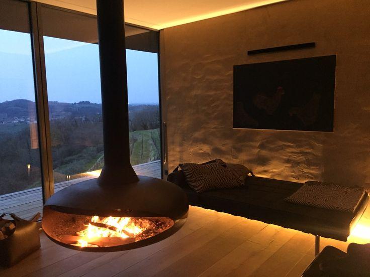 Dieser frei im Zimmer hängende Stahlkamin ist durch sein attraktives Design der Mittelpunkt des Hauses. Die wohlige Wärme lässt Körper und Geist zur Ruhe kommen. #offener Kamin #moderner Kamin #Feuerstelle #Fireplace #Ofenkunst www.Ofenkunst.de