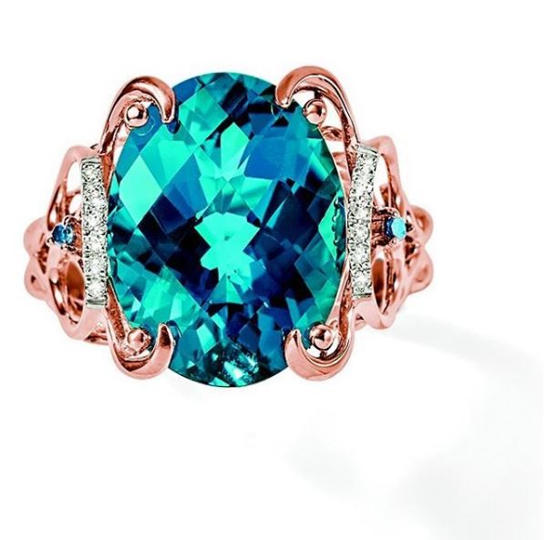 This 10.00 carat oval London blue topaz ring is accented with white and treated blue diamonds. It is set in 14kt rose gold openwork that adds a fun flair to an already unique ring! Item no. 873179