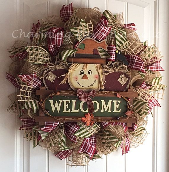 This adorable scarecrow wreath is just too cute and a must have addition for your fall decor. Wooden scarecrow holding a Welcome sign with