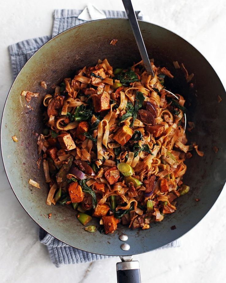 rice noodles, eggplant, tofu, and Thai basil all together in a wok getting tossed with a pair of tongs
