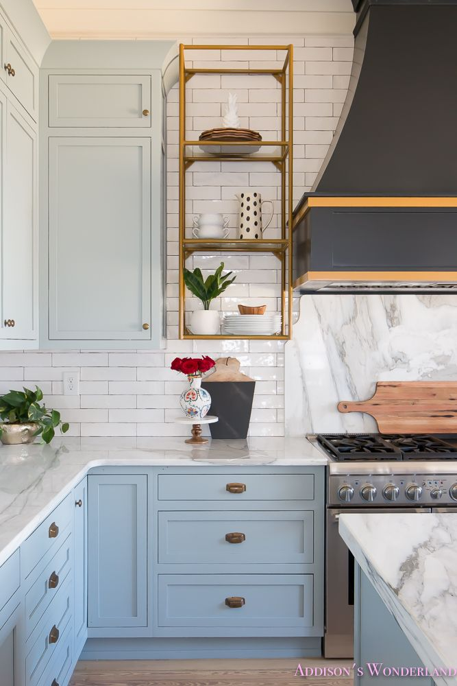 Designer tips on styling open kitchen shelving! How to select the best accessories for your space... kitchen-white-marble-calcutta-gold-open-shelves-gold-black-vent-hood-blue-gray-cabinets-shaker-style-black-chevron-tile-subway-white-backsplash-decor-ide