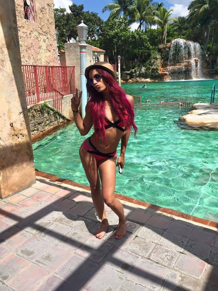 Sasha Banks barefoot and in a bikini by the pool.