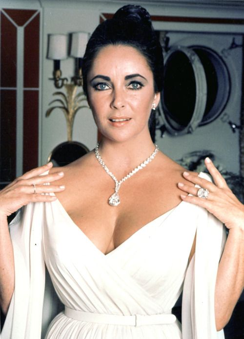 ELIZABETH TAYLOR WEARING HER SMALLEST AND BIGGEST DIAMONDS, THE PING-PONG DIAMOND RING ON HER RIGHT HAND, AND THE KRUPP DIAMOND ON HER LEFT, WITH THE TAYLOR-BURTON ICEBERG ON HER NECK, FOR GRACE KELLY'S 40TH BIRTHDAY.