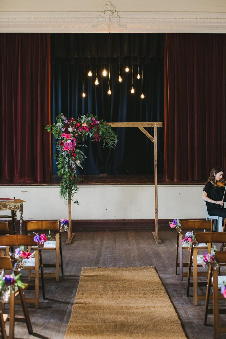 town hall wedding with jewel-toned floral arbour