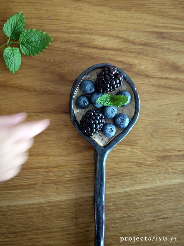 berries and blackberries in the  black and white  ceramic spoon