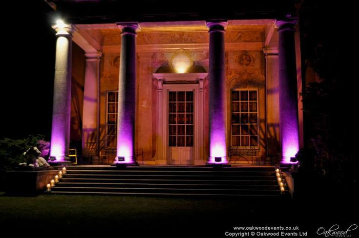 Flood lighting in pink on the pillars and gold under the portico on the West Wycombe estate for a marquee wedding