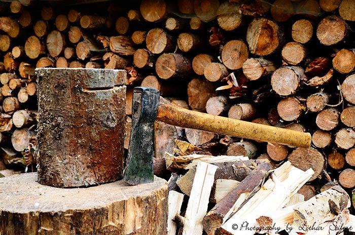 Brennholz spalten mit einer Axt auf einem Hackeklotz aus einem Eichenstamm. Fotografie von Lothar Seifert