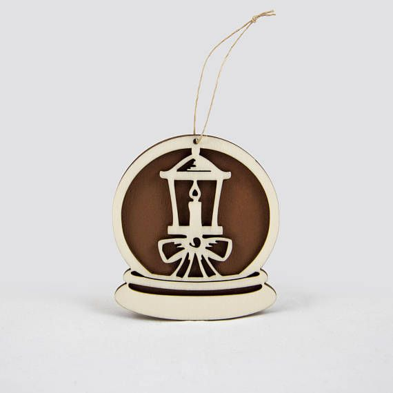 Wooden snow globe Christmas ornament with a lantern.