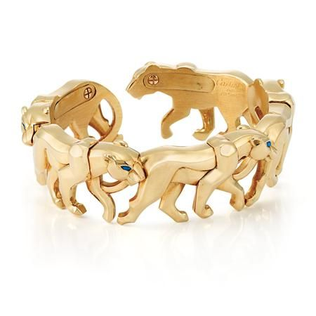Gold Panther Bangle Bracelet, Cartier   18 kt., composed of five pacing panthers, accented by 5 marquise-shaped sapphire eyes, with open back, signed Cartier, # 704987, approximately 61 dwt. Inner circle 6 inches.