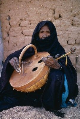 Niger, Tribal Music, Tuareg Woman Playing An Imzad. Traditional Instrument Consisting Of A Goatskin Covered Gourd Or Wooden Resonator Played With A Curved Bow And Horsehair String. - stock photo