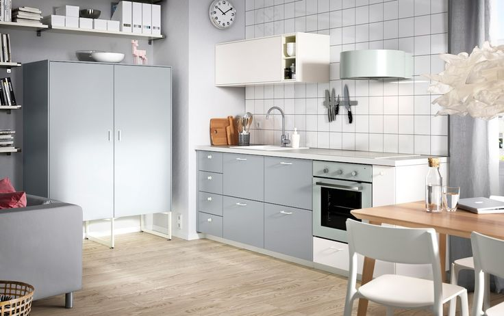A kitchen with white doors and grey drawers combined with grey-green appliances.