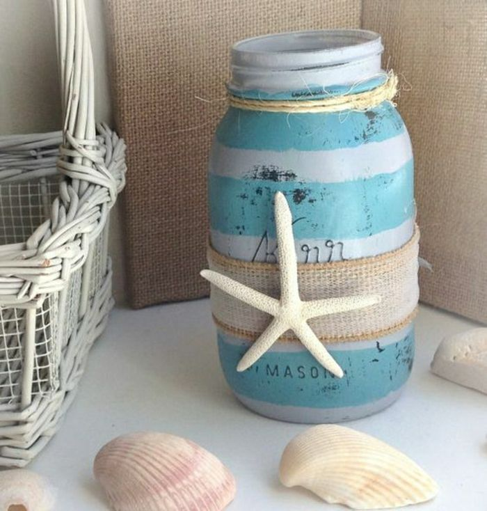 summer crafts for adults, open mason jar, painted in turquoise and light blue stripes, decorated with burlap and a single dried starfish, white whicker basket, and several seashells nearby