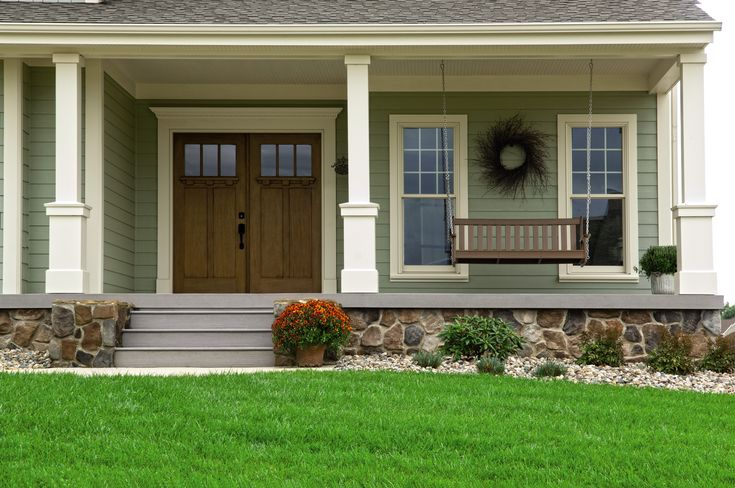 Beautiful double doors and a porch swing as a welcoming entrance.