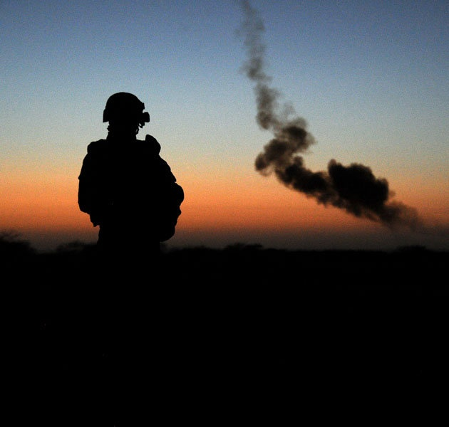A French soldier looks at smoke from a controlled explosion of a device found by the French armed forces in Gao on February 14, 2013.