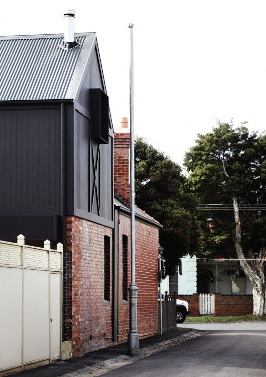 addition - dark painted wood and metal profiled roof over existing red brick