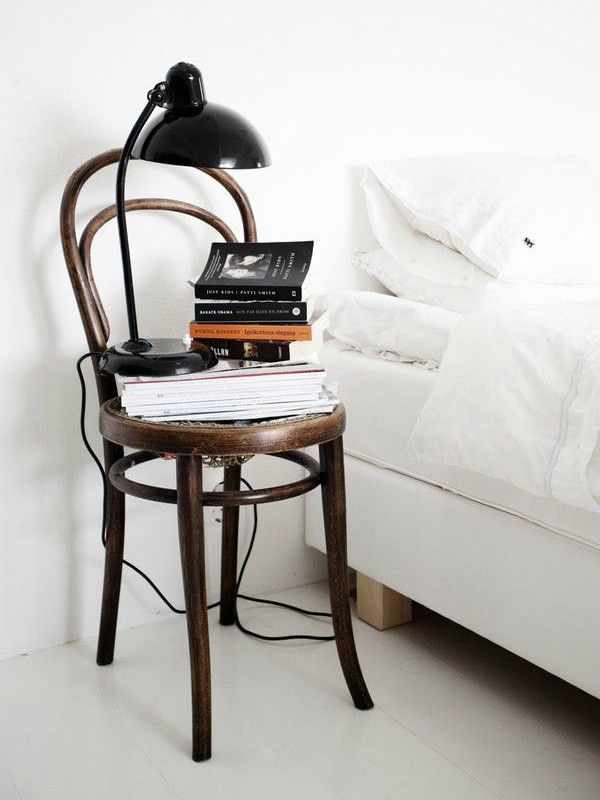 7 crazy cool bedside table ideas // Distressed chair with magazine stacks and a chic lamp