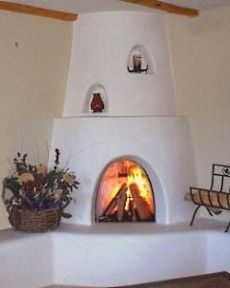 This kiva fireplace has all the design elements--raised hearth and banco, mantel and nichos. Lovely!