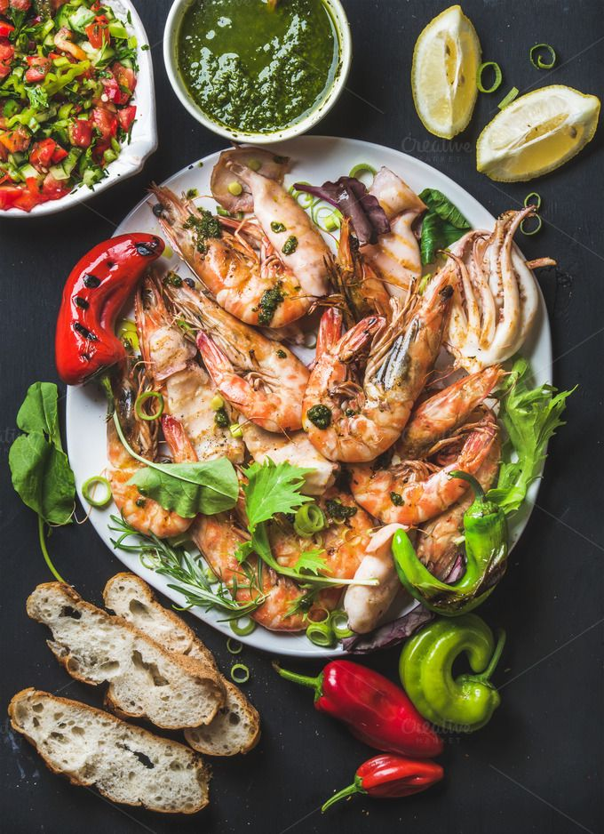 #Plate of roasted tiger prawns  Plate of roasted tiger prawns and pieces of octopus with fresh leek vegetable salad peppers lemon bread and pesto sauce over black background top view vertical composition