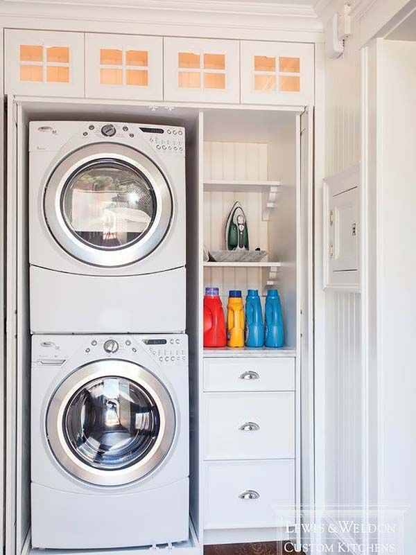 Use slide out doors.  Put on sides of washer dryer, which will allow for cabinets along wall in front along the door wall.  Washer and dryer will open towards hot water heater.  Put all electronics in small cabinet above washer to hide.