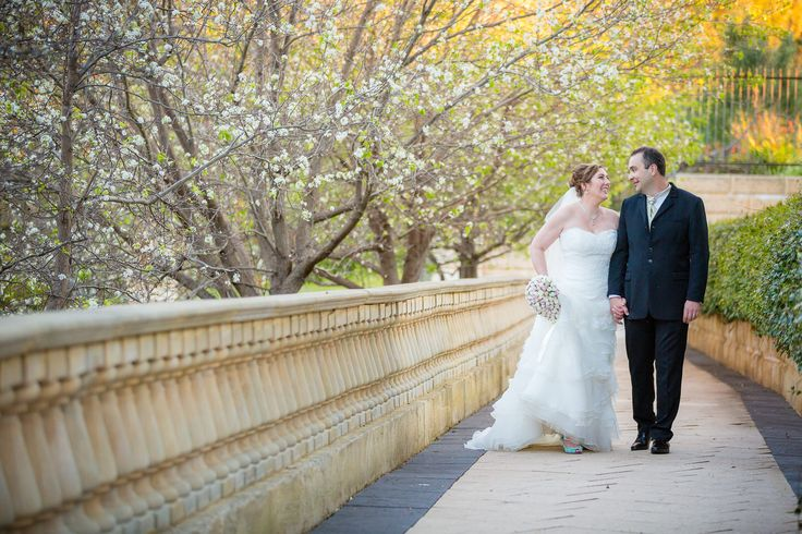 The wedding couple is taking a walk in between blooming trees at the Caversham House.