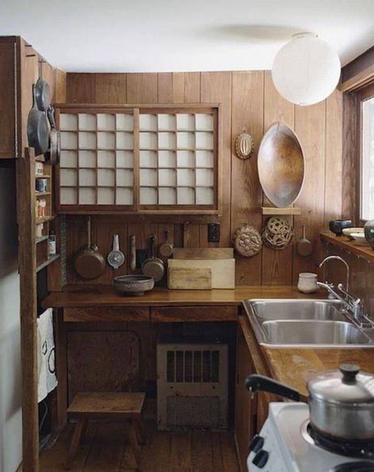This is a smaller and more unique Japanese kitchen. In this picture you can see a counter, a sink, pots and pans, and cooking materials.