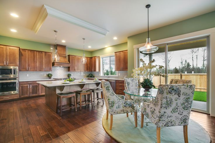 A wonderful Kitchen and Eating Area combination. Beautifully patterned chairs with a glass table off of the kitchen serves as the perfect breakfast area. The rich brown kitchen cabinets work wonderfully with the amazing granite kitchen island as well
