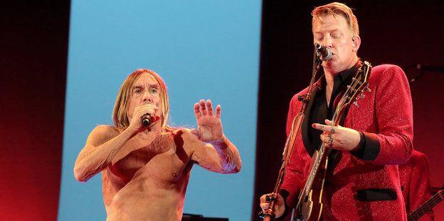Zwei Männer auf einer Bühne: Einer singt und ist oberkörperfrei, es ist Iggy Pop, der andere trägt einen roten Anzug, singt und spielt Gitarre, es ist Josh Homme.