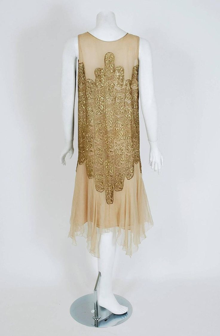 Evening dress 1925 Elspeth Champcommunal metallic gold-lame and champagne silk-chiffon dress. The lame has a floral embroidered pattern. The dress has layered handkerchief skirting and scalloped art-deco work. Garment slips over head with no additional closures. Elspeth Champcommunal was a British fashion designer and the first editor of Vogue in Britain. She was influential as a designer in her own right in Paris, later taking on the role of chief designer of Worth Back 2