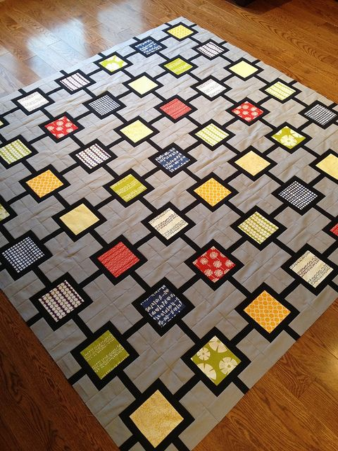 "A good way to make a quilt with a charm square set -- or to feature bigger prints. the clever setting can be unit-pieced, and this gray and black sets off the ""medium"" colors."
