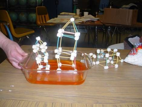 A photograph of an assembled, homemade structure constructed out of marshmallows and toothpicks. The structure is sitting on a bed of orange...